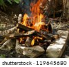 Camping Fire into Stones closeup outdoors - stock photo
