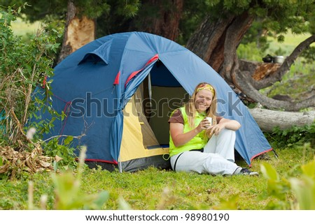 Camping happy woman drinking tea in front of tent - stock photo