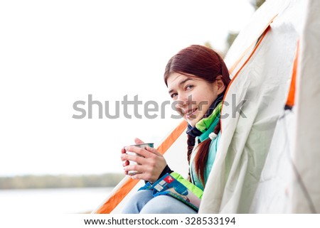 Camping happy woman sitting tent, drinking tea in park  - stock photo