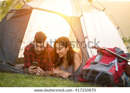 Camping hipster couple in tent taking selfie using smartphone