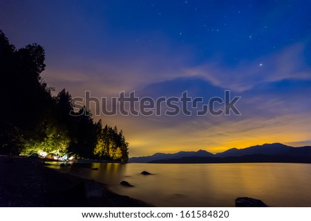 Camping in tents next to lake with Blue and Orange night sky. - stock photo