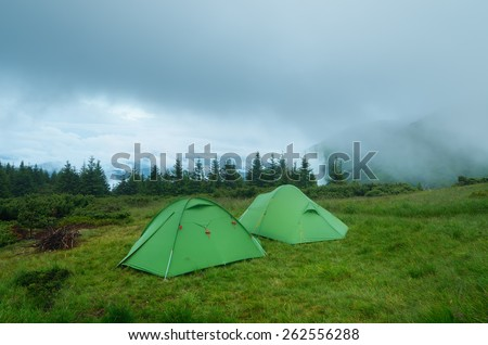 Camping in the mountains. Two green tourist tents. Evening landscape with cloudy sky. - stock photo