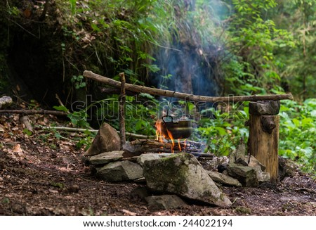 Camping kettle over burning campfire  - stock photo