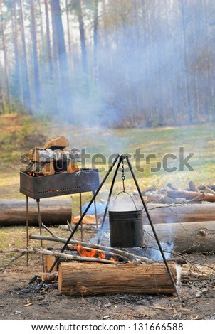 Camping kettle over burning campfire in the day light - stock photo