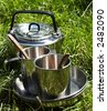 Camping kitchenware in grass - stock photo