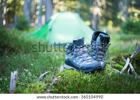 Camping people putting on hiking shoes by tent