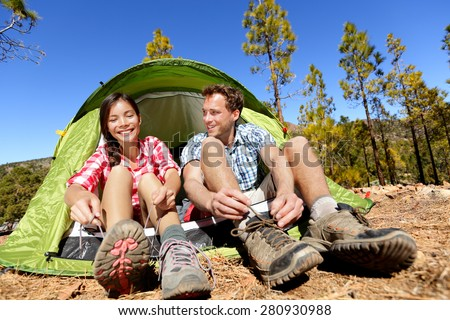 Camping people putting on hiking shoes by tent. Campers tying shoe laces getting ready for hike. Asian woman and Caucasian man living fun active lifestyle outdoors. - stock photo