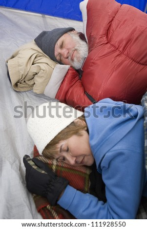 Camping senior couple sleeping in tent