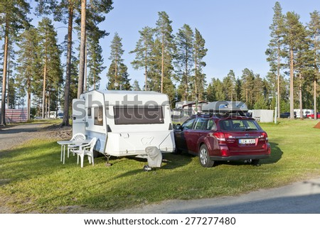 CAMPING, SWEDEN ON JUNE 25. View of a campsite, car and caravan on June 25, 2012 in Sweden. Evening lit over the area, camping, pines and lawn.