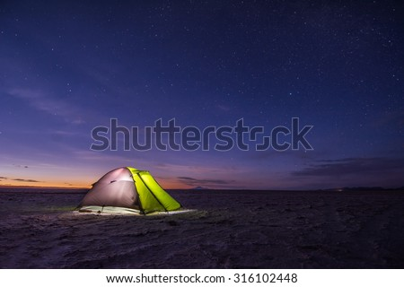Camping tent at night against amazing sky full of stars, Salar de Uyuni, Bolivia - stock photo