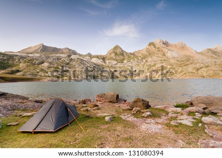 Camping Tent by Estanes Lake during sunrise. Spanish Pyrenees. - stock photo