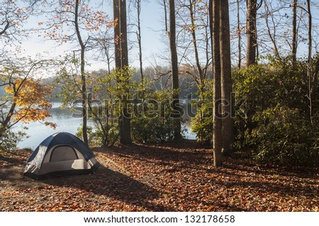 Camping tent in the woods by the lakeside - stock photo