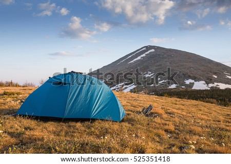 Camping tent near high moutain in the evening sunset time, Ural, Russia