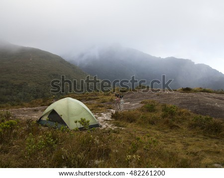 camping tent on a cloudy and rainy day in the mountain with fog - nature landscape