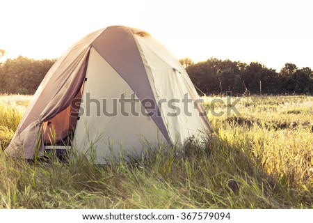 camping tent on summer meadow during sunset with back sunlight and copy space - stock photo
