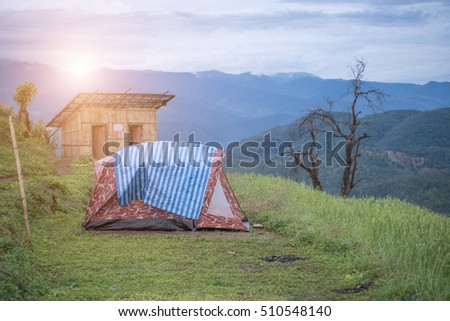 camping tent on summer meadow during sunset with back sunlight and copy space