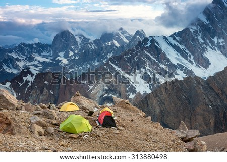 Camping Tents and High Mountain View Twilight Panorama of Fan Mountains Valley with Alpine Camp on Rock Moraine Foreground - stock photo
