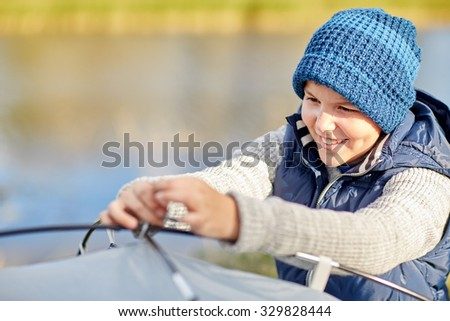camping, tourism, hike and people concept - happy boy setting up tent outdoors - stock photo