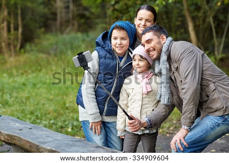 camping, tourism, hike, technology and people concept - happy family taking picture with smartphone on selfie stick at camp