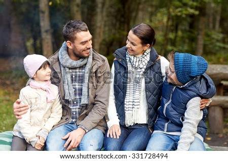 camping, travel, tourism, hike and people concept - happy family sitting on bench and talking at camp in woods