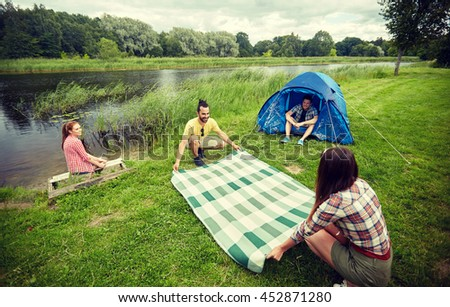 camping, travel, tourism, hike and people concept - happy friends with tent laying picnic blanket at campsite on river bank - stock photo
