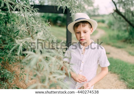 Camping under the trees boy in a straw hat and a white shirt - stock photo
