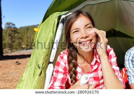 Camping woman applying sunscreen sun cream sunblock suntan lotion in tent smiling happy outdoors in forest. Happy biracial Asian Caucasian girl living healthy active lifestyle. - stock photo