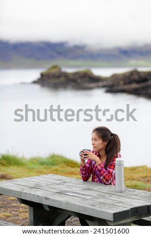 Camping woman sitting at table drinking coffee from thermos bottle flask by lake on Iceland. Camper girl relaxing thinking pensive taking break on road trip in beautiful Icelandic nature. - stock photo