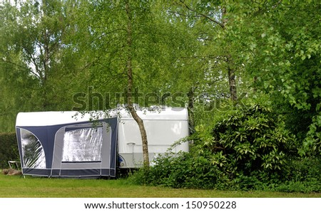 Campside with caravan and a small forest  - stock photo