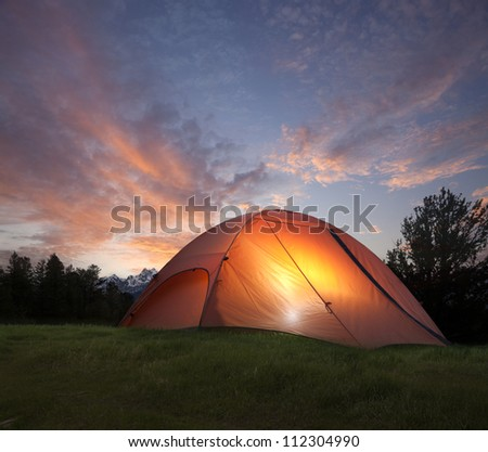 Campsite with illuminated orange tent in the Grand Tetons at sundown