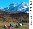 Campsite with tents on the top of high mountains, covered by snow. Kangchenjunga, India. - stock photo