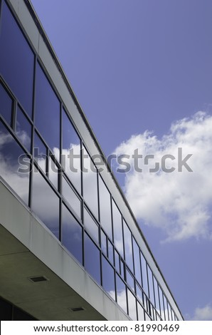 Campus reflections: Windows of long university building reflect white cloud in blue  sky