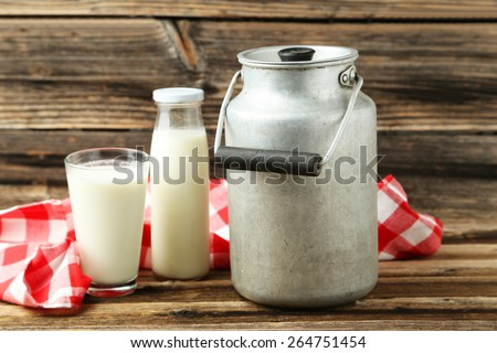 Can and glass of milk on brown wooden background - stock photo