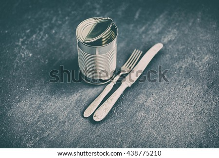 Can and tableware against a dark background. Vintage toning - stock photo