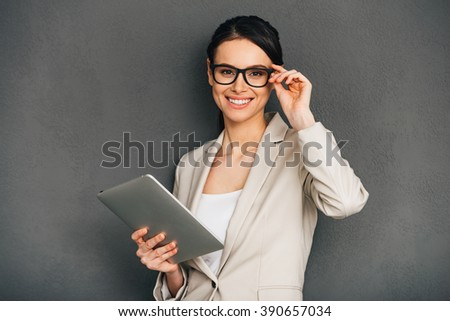 Can I help you? Beautiful young cheerful businesswoman adjusting her glasses and holding digital tablet while standing against grey background - stock photo
