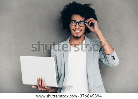 Can I help you? Cheerful young African man using laptop and looking at camera while standing against grey background - stock photo