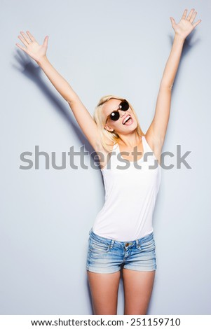 Can not hide her emotions. Beautiful young blond hair women keeping arms raised and smiling while standing against grey background   - stock photo