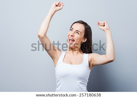 Can not hide her emotions. Beautiful young women keeping arms raised and smiling while standing against grey background   - stock photo