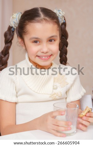 Can not stop drinking milk. Small smiling girl holding an empty glass of milk and biscuit - stock photo