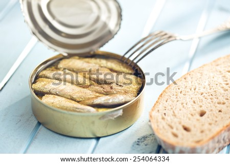 can of sprats on kitchen table - stock photo