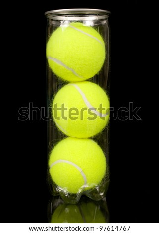 Can of three new tennis balls isolated on black background.