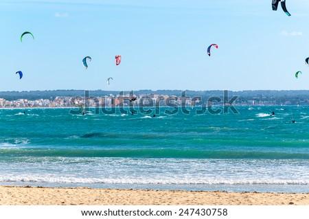 CAN PASTILLA, MAJORCA, SPAIN - FEBRUARY 10 2013: Kite surfers enjoying tourist free sunny winter beach on February 10, 2013 in Can Pastilla, Majorca, Spain.  - stock photo