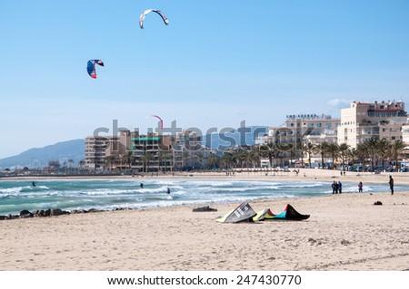 CAN PASTILLA, MAJORCA, SPAIN - FEBRUARY 10 2013: Surfers enjoying tourist free sunny winter beach on February 10, 2013 in Can Pastilla, Majorca, Spain.  - stock photo
