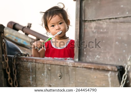 CAN THO, VIETNAM, DECEMBER 12, 2014: A little girl is brushing her teeth on a family boat in the Cai Rang floating market on the Mekong river in Can Tho city, Vietnam. - stock photo
