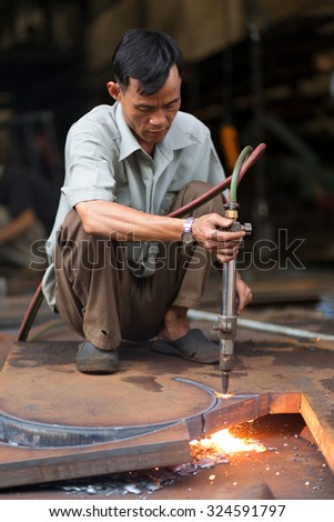CAN THO, VIETNAM, DECEMBER 11, 2014 : A man is welding a metallic structure without any protection in the market of Tan An in Can Tho, Vietnam