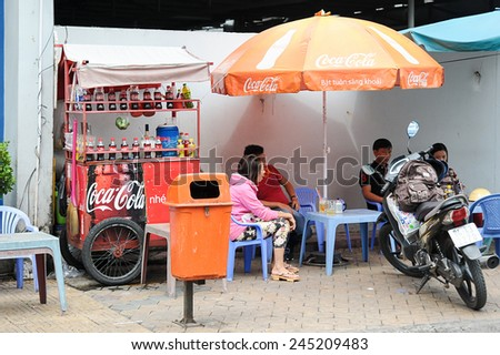 Can Tho, Vietnam. June 14, 2014 : Unidentified customers having a break at streets stall with Coca Cola push cart and umbrella at Can Tho, Vietnam on June 14, 2014.