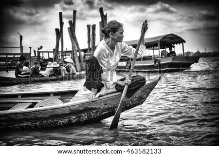 Can Tho, Vietnam - March 13, 2016: Vietnamese Woman row on a wood boat on Cai Rang floating market in the Mekong Delta. Sunset light, black and white picture