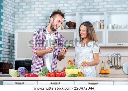 Can we add the cucumber. Young and beautiful couple in love cooking vegetables and help each other while breakfast is prepared with vegetables in the kitchen. - stock photo