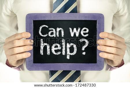 Can we help ? handwritten on blackboard  - stock photo