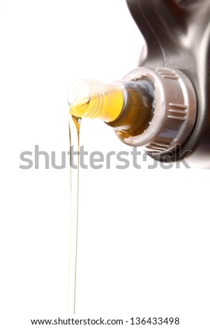 Can with car engine oil pouring in front white background - stock photo